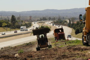 Construction workers began cleaning up hillside in preparation of Phase 1: Widening of Baseline Bridge over E. 210 freeway.